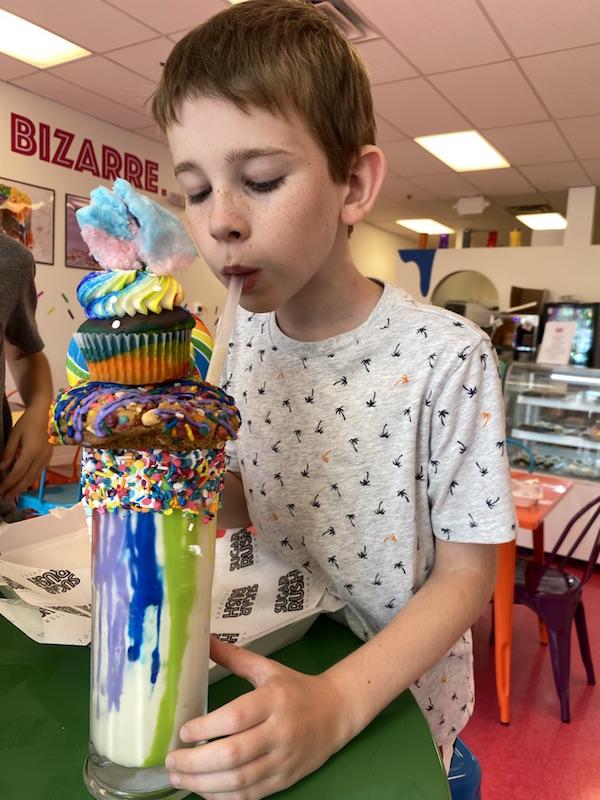 Boy drinking an extreme milkshake at Sugar Rush in Columbus, Ohio.